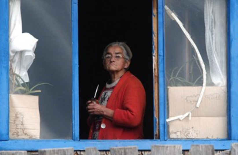 Elderly woman looks out of window [illustrative] (photo credit: Ivan Alvarado / Reuters)