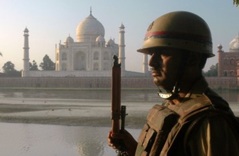 An Indian police officer standing guard 390 (R) (photo credit: Stringer India / Reuters)