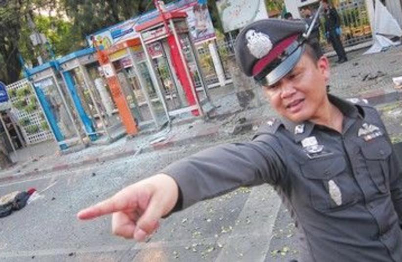 Thai policeman at the scene of Bangkok bombing 390 (R) (photo credit: Damir Sagolij/Reuters)