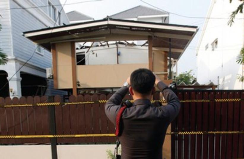 Thai policeman takes photo of terror site_390 (photo credit: Reuters)