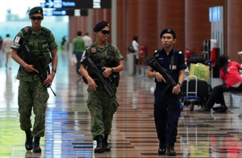 Singapore soldiers patrolling 390 (photo credit: REUTERS/Vivek Prakash)