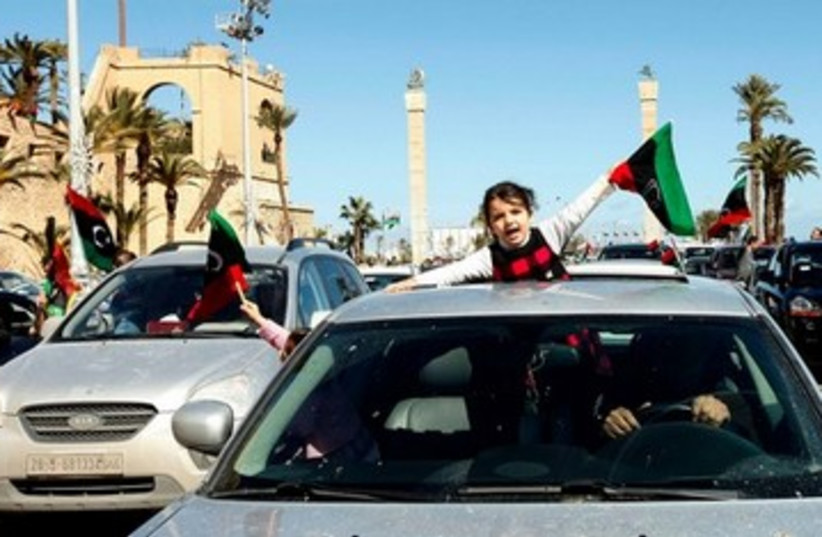Girl waves a Libyan independence flag 390  (photo credit: REUTERS)