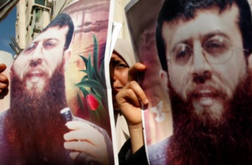 Palestinians holding poster of Khader Adnan 390 (R) (photo credit: REUTERS/Ibraheem Abu Mustafa)
