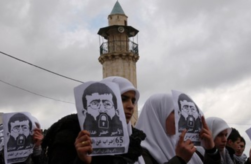 Palestinian students hold signs depicting Khader Adnan 390 R (photo credit: REUTERS/Abed Omar Qusini)