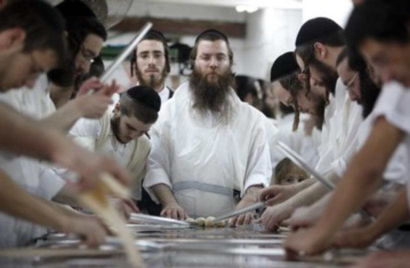 Orthodox men prepare matza 390 (R) (photo credit: NIR ELIAS / Reuters)