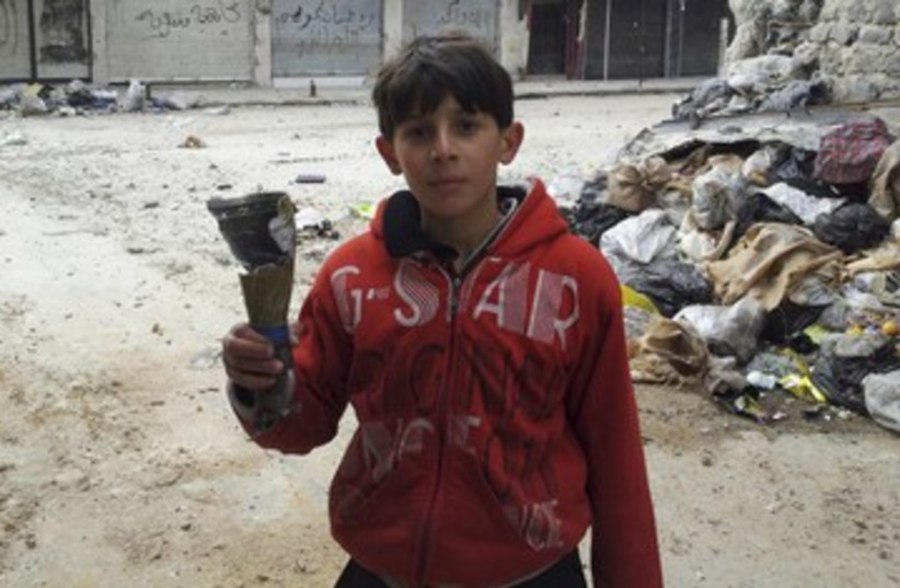 Boys hold remains of mortar in Homs neighorhood R 390 (photo credit: REUTERS)