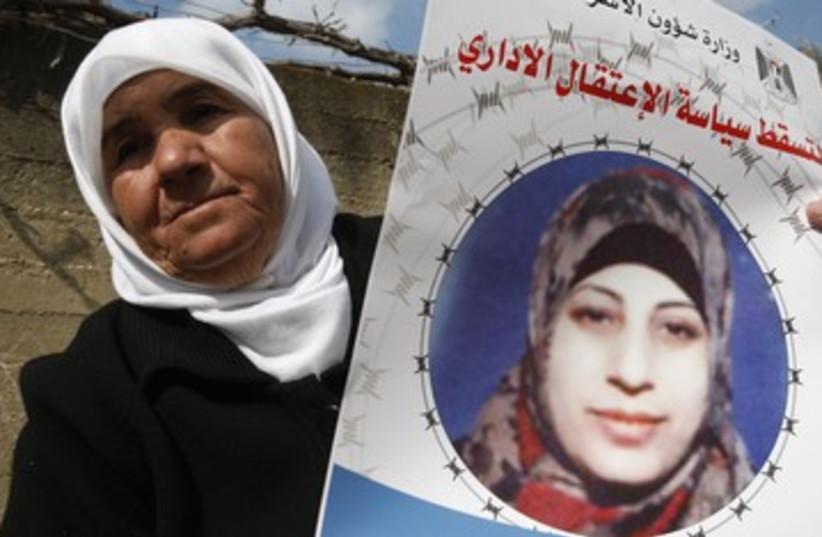 Badeeah Shalabi holds a placard of her daughter Hana 390 (photo credit: reuters)