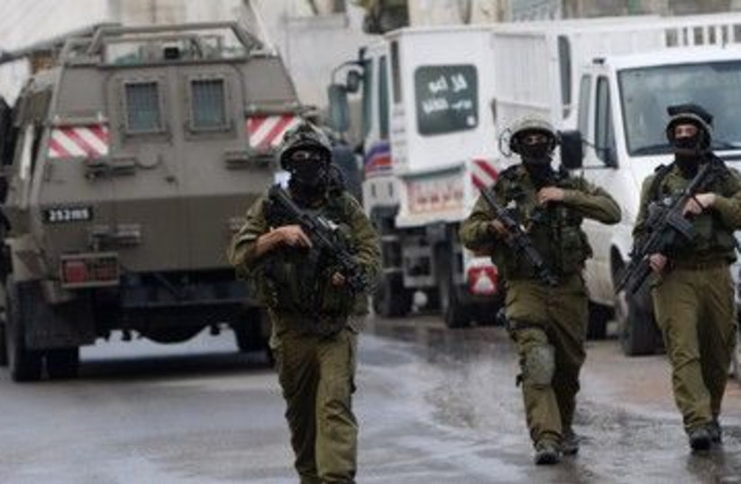 IDF soldiers patrol during a raid 390 (R) (photo credit: Abed Omar Qusini / Reuters)