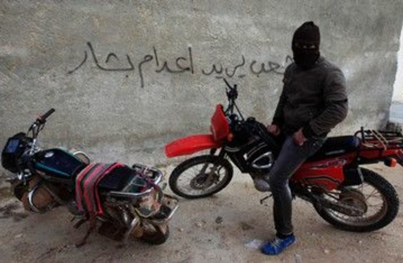 Free Syrian Army member on a motorcycle 390 (R) (photo credit: REUTERS/Zohra Bensemra)