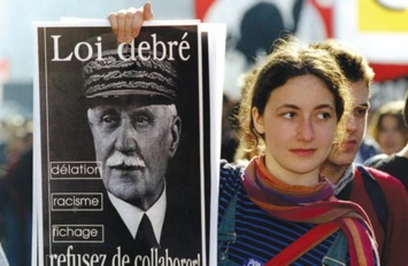 Protester holding up sign of Philippe Petain (photo credit: Reuters)