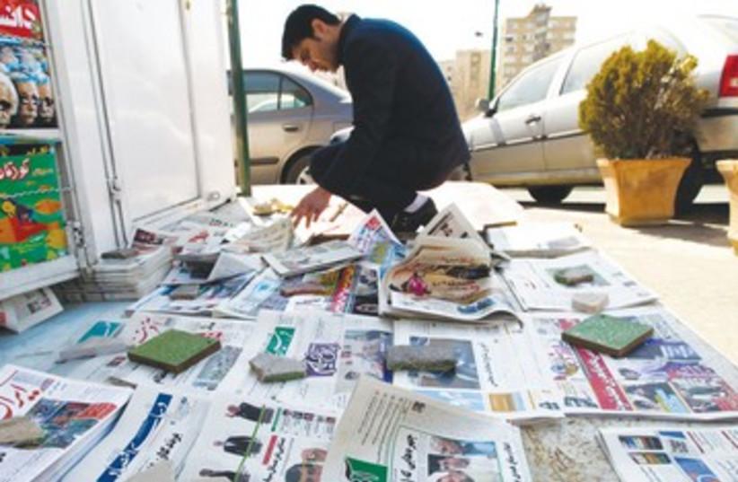A man looks at a newspaper in Tehran R 390 (photo credit: Raheb Homavandi/Reuters)