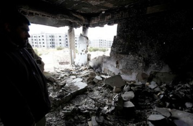 Syrian man surveys his damaged home 390 (R) (photo credit: REUTERS/Anis Mili)
