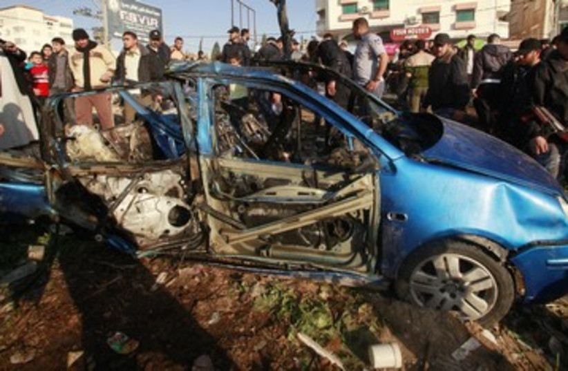 Palestinians look at the remains of exploded vehicle 390 R (photo credit: REUTERS)