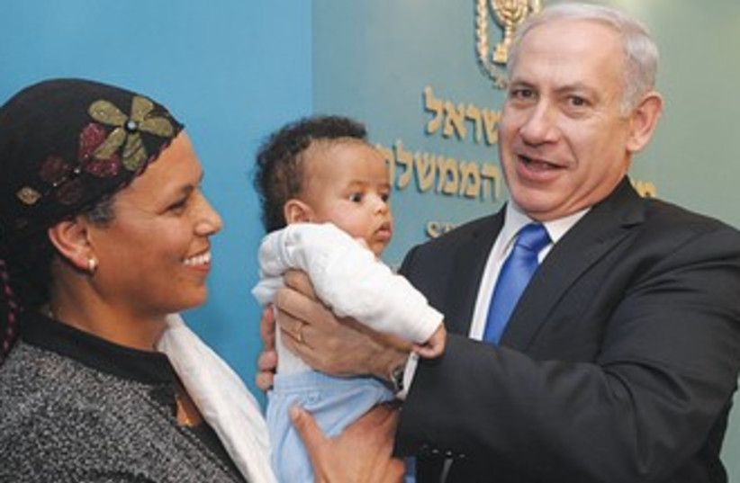 PM holds Ethiopian baby at Knesset 390 (photo credit: GPO)
