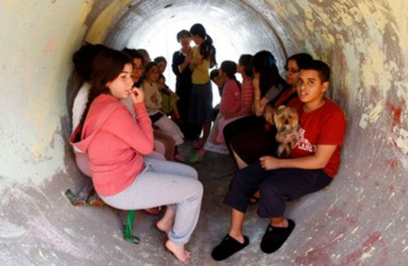 Children take shelter from rockets in a sewage pipe 390 (R) (photo credit: REUTERS/Baz Ratner)