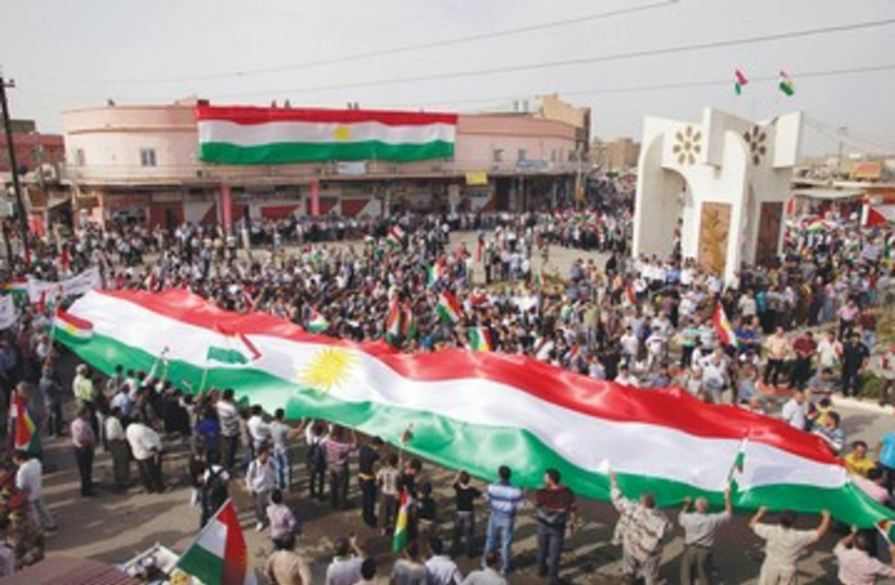 Iraqi Kurds waving flags 390 (photo credit: REUTERS)