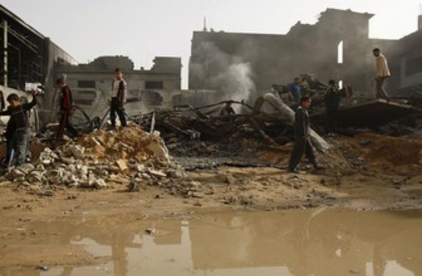 Palestinians walk past rubble from IAF air strike, Gaza_370 (photo credit: Ibraheem Abu Mustafa/Reuters)