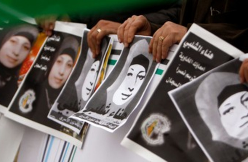 Palestinian protesters hold pictures of Hana Shalabi 370 R  (photo credit: REUTERS)