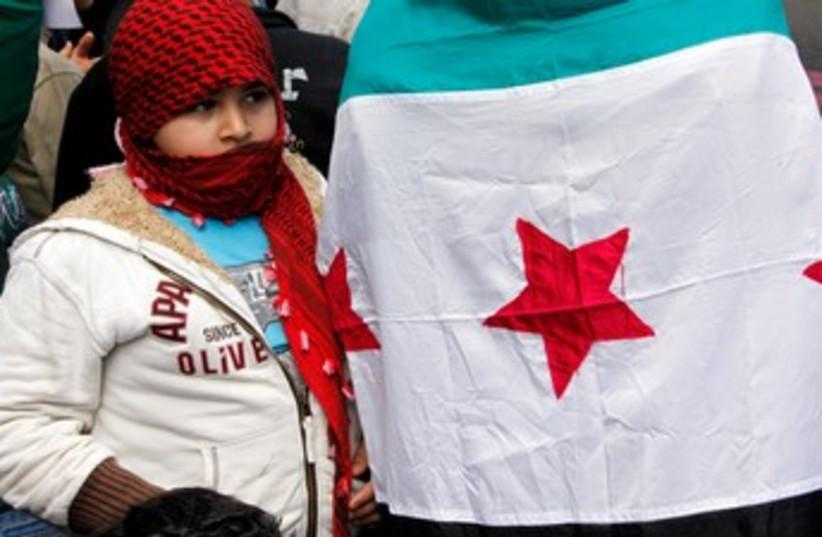 Child near Syria opposition flag 370 (photo credit: MOHAMED AZAKIR)