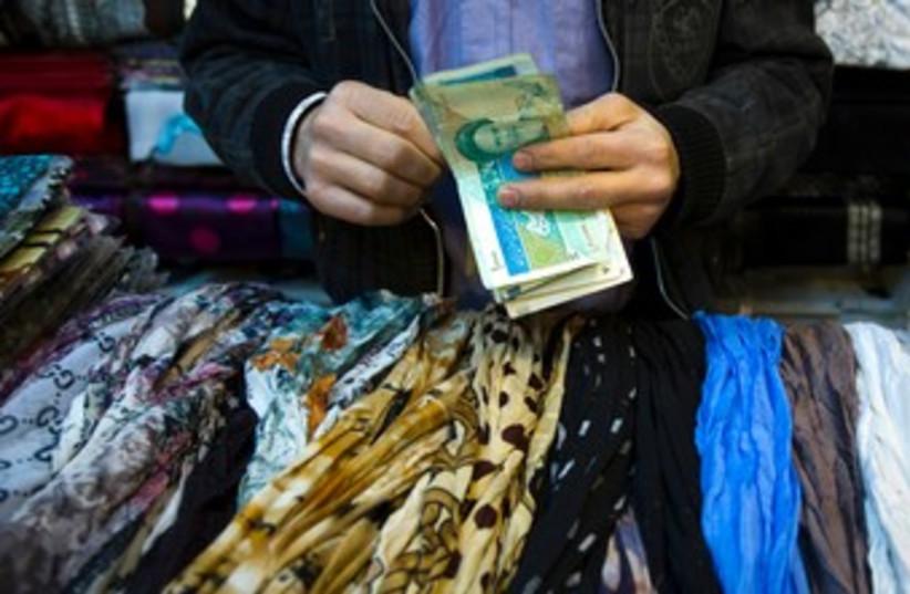 Iranian handles money at bazaar 370 (photo credit: REUTERS)