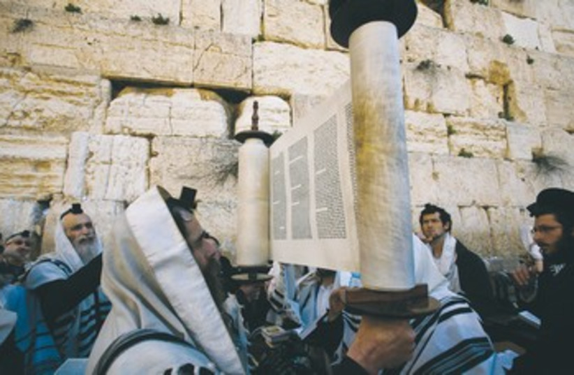 A worshiper holds up a Torah scroll 370 (photo credit: Reuters)