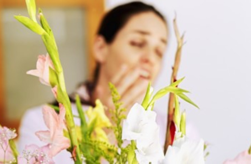 Young woman sneezing in front of a bouquet of flowers 370 (photo credit: Thinkstock/Imagebank)