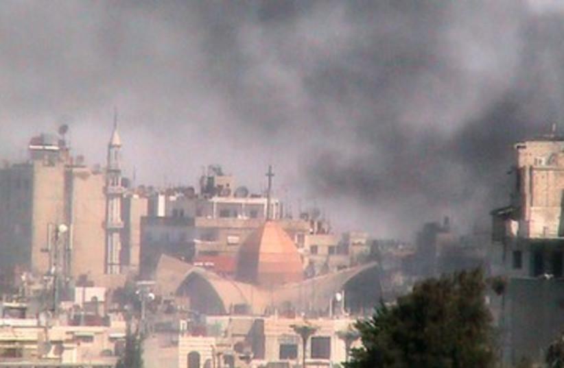Smoke rises from the Bab Sabaa neighbourhood of Homs 390 (R) (photo credit: REUTERS/Shaam News Network/Handout)