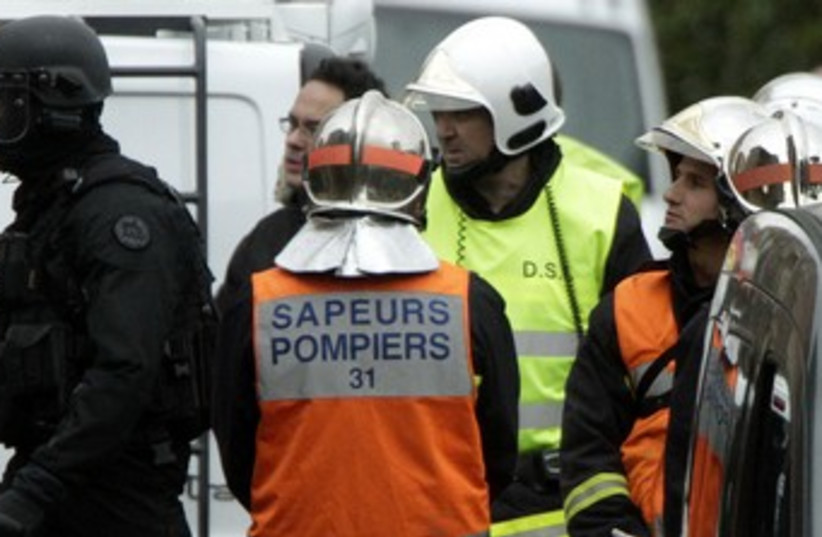 Firemen, special unit police outside French Shooter apt 370 (photo credit: REUTERS/Jean-Philippe Arles )
