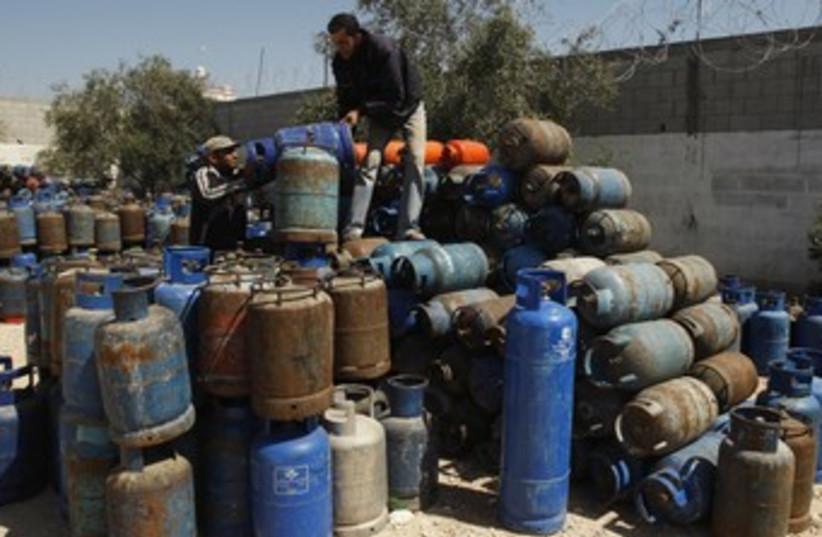 Gazans arrange gas cylinders at gas filling station  R (photo credit: REUTERS)