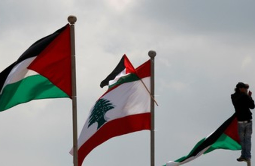 Man atop flag pole in Land Day protest in Lebanon 370 (photo credit: REUTERS)