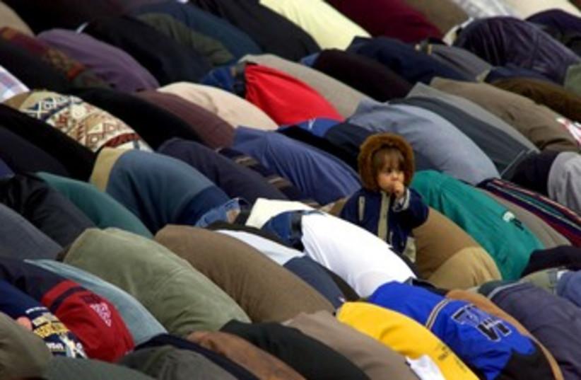 Child amongst crowd of praying Muslims 370 (photo credit: REUTERS/Radu Sigheti)