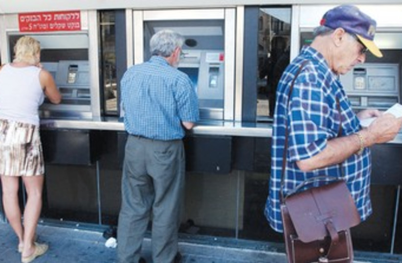 People make transactions at Bank Hapoalim ATM 370 (photo credit: Ariel Jerozolimski)