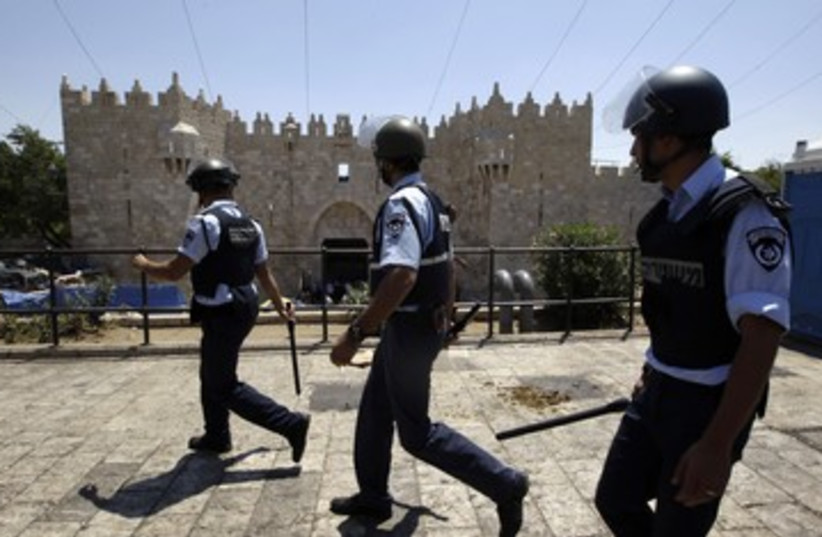 Police walk near Jerusalem's Damascus Gate 390 (R) (photo credit: Ammar Awad / Reuters)