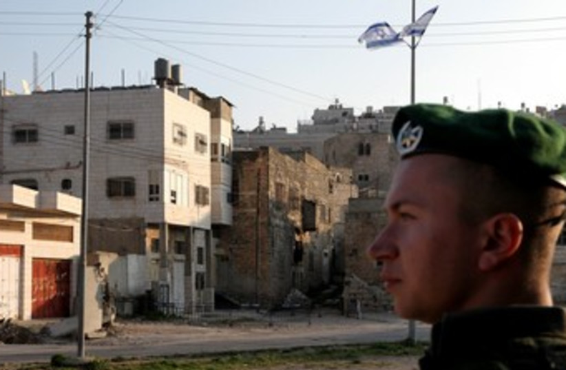 IDF soldier stands guard near Beit Hamachpela_370 (photo credit: Marc Israel Sellem/The Jerusalem Post)