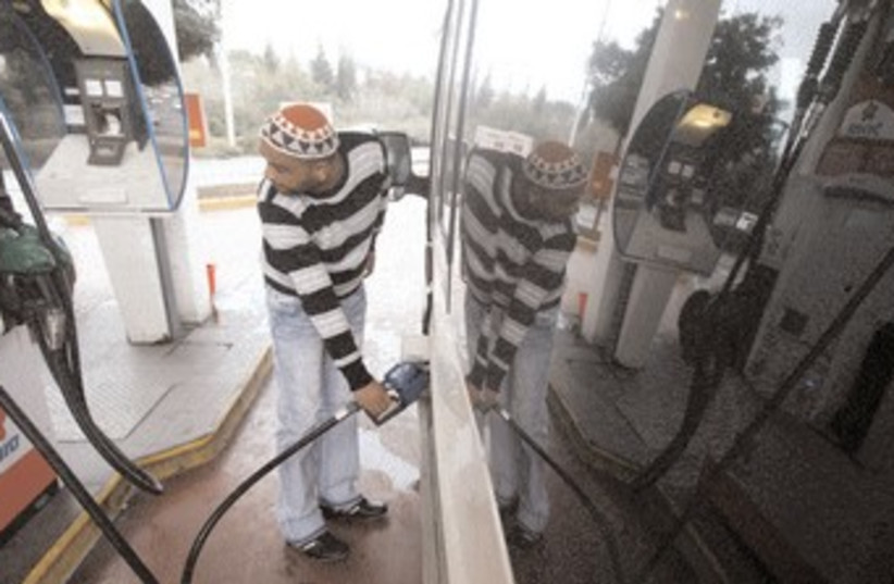 A man pumping gasoline at a gas station 370 (R) (photo credit: Reuters)