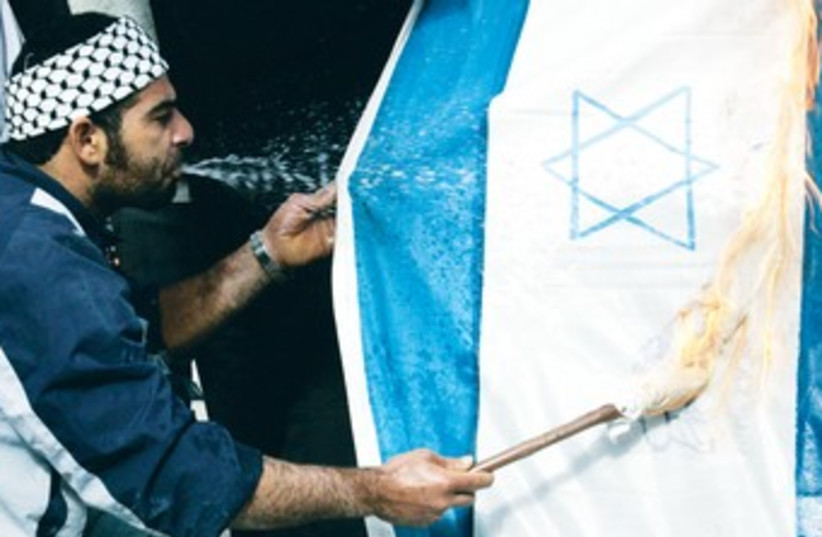 Palestinian man spits gasoline on Israeli flag 370 (R) (photo credit: Reuters)