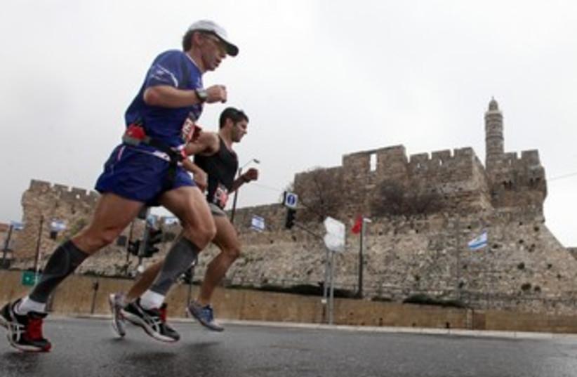 Runners in Jerusalem Marathon pass Old City 370 (photo credit: Marc Israel Sellem)