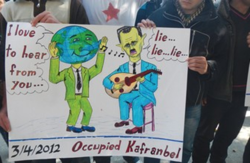 Demonstrators hold sign at protest in Kafranbel, near Idlib  (photo credit: reuters)