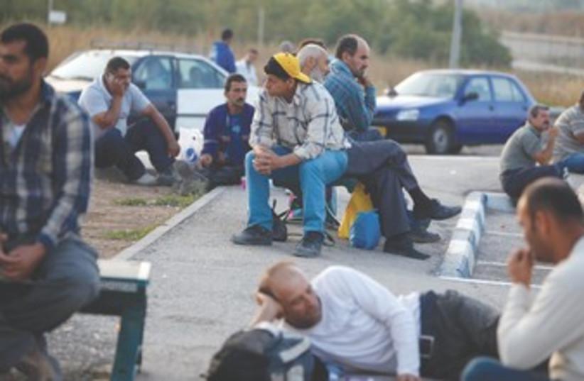 Working class Palestinians sitting around 370 (photo credit: REUTERS)