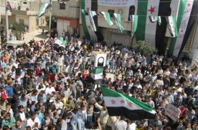 Syrians demonstrate near Homs 370 (R) (photo credit: REUTERS/Shaam News Network)