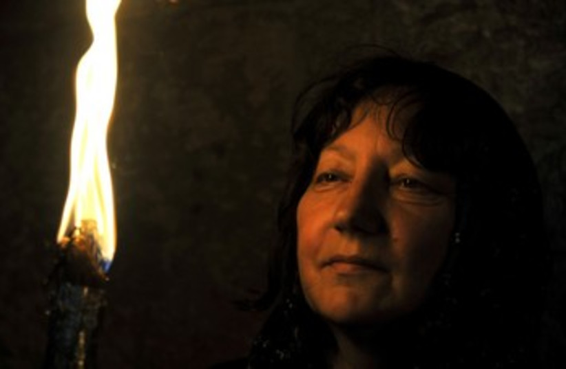Woman looks at Holy Fire on Holy Saturday 370  (photo credit: Hadas Parush)