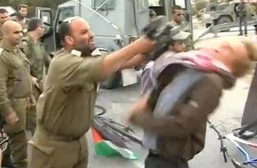 IDF officer hitting activist with M-16 370 (photo credit: YouTube Screenshot)