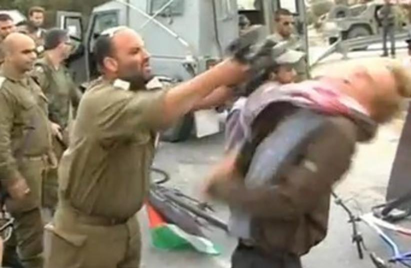 IDF officer hitting activist with M-16 370 (photo credit: YouTube Screenshot)