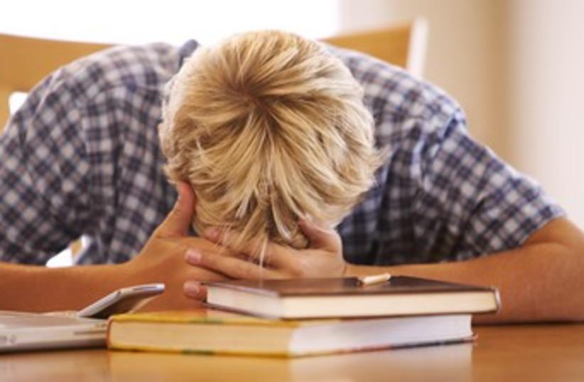 Stressed boy with head in books 370 (photo credit: Thinkstock/Imagebank)