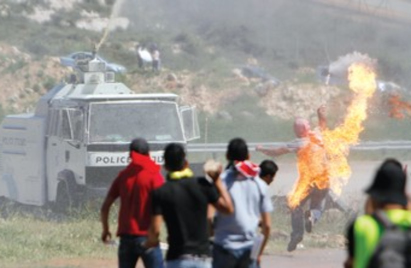 Stone-throwing Palestinian 370 (photo credit: Reuters)