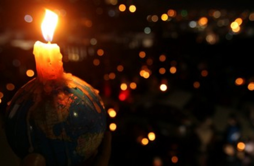 People hold candles during Earth Hour (photo credit: REUTERS/Ali Jarekji)
