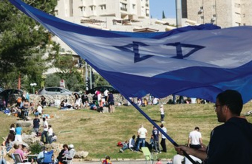Man waves Israeli flag in Jerusalem 370 (photo credit: Marc Israel Sellem)