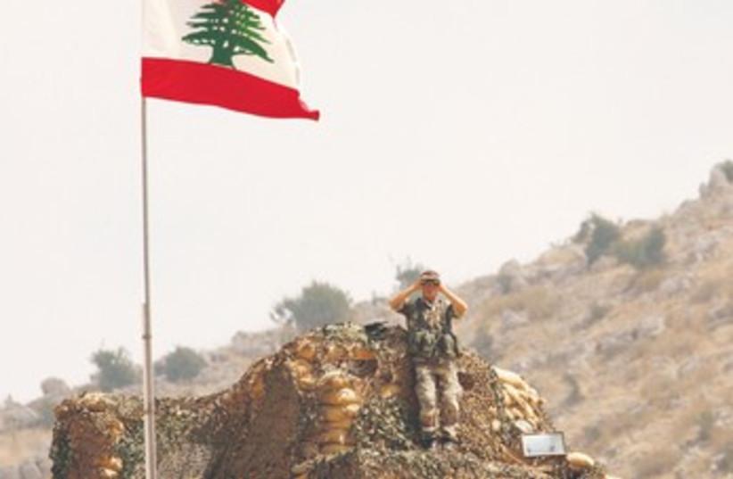 Lebanese soldier peers at Israel along border 370 (photo credit: Ali Hashisho/Reuters)