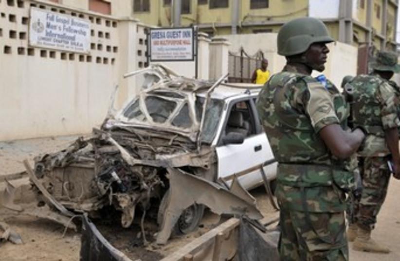 Nigerian soldiers at bomb site near Abuja 370 (photo credit: REUTERS/Afolabi Sotunde)