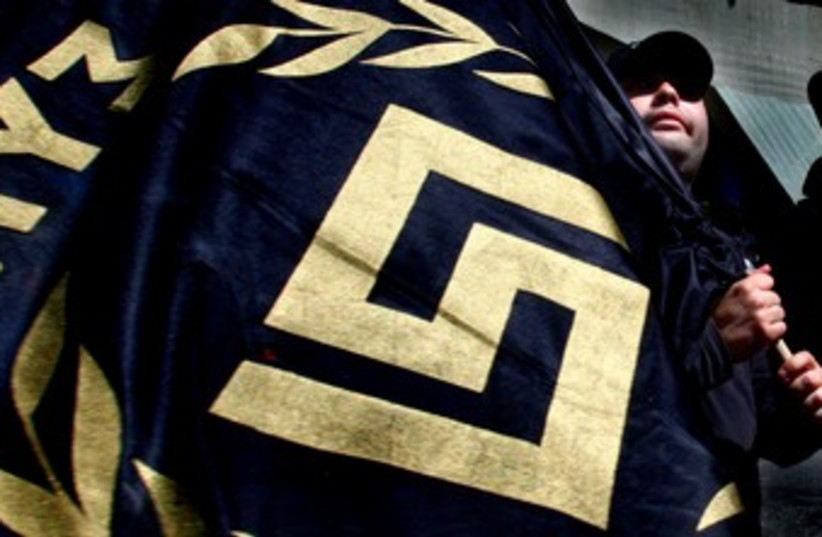 Golden Dawn party activist waves flag with party logo 370 (photo credit: REUTERS/Yannis Behrakis)